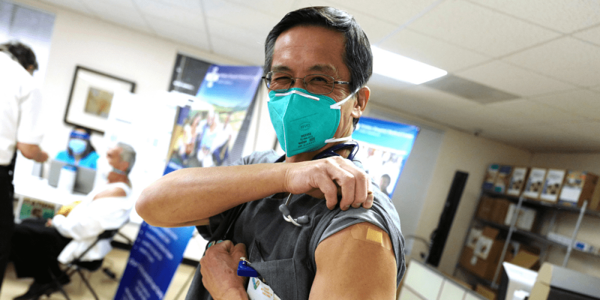 A doctor lifting up his left shoulder sleeve to show a bandage signaling that he has received a COVID-19 vaccine